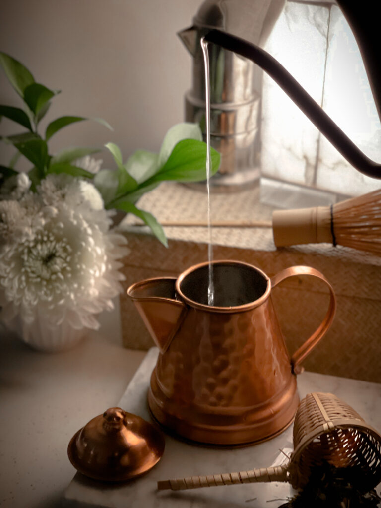 Easy Steps to create a Cozy Home 2.  Water pouring into a tea kettle and flowers in the background.