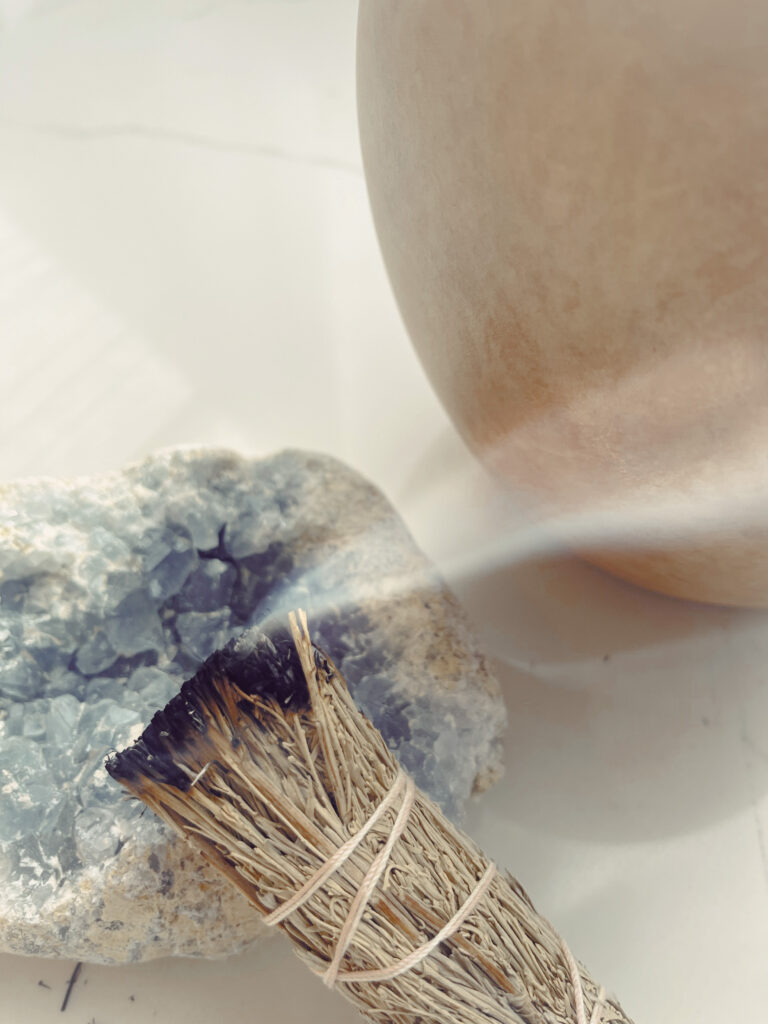 Easy Step to create a Cozy Home 3. Sage bundle burning on a crystal.