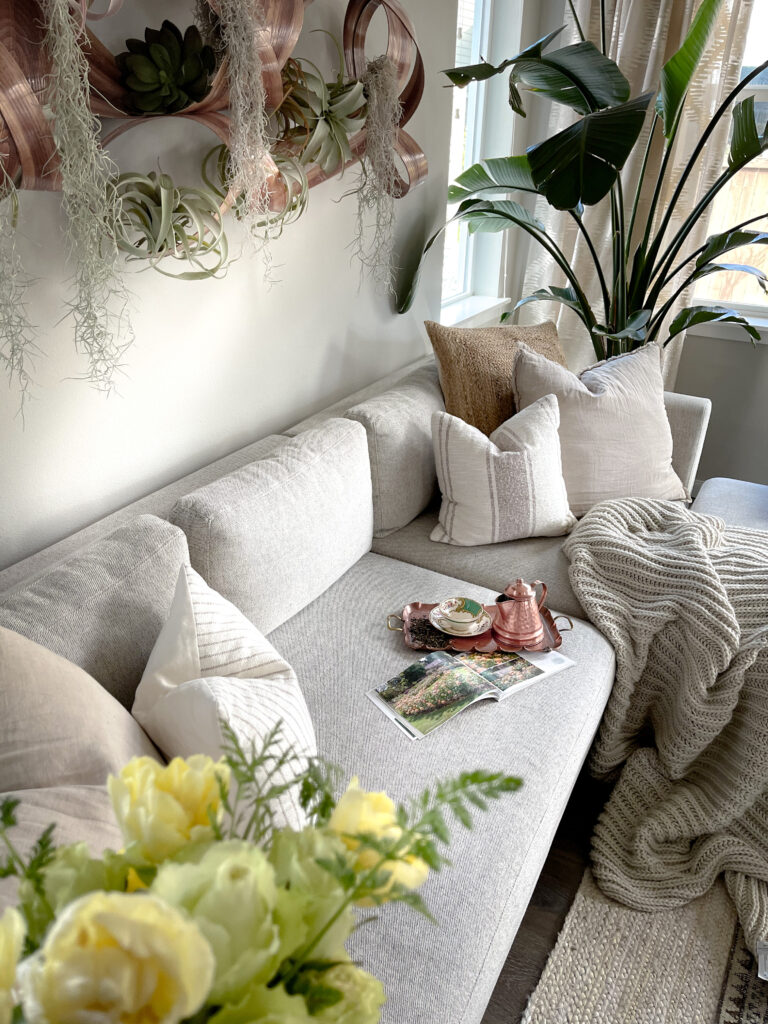 Easy Steps to Create a Cozy Home showing Sofa Setting with flowers, tea tray and a cozy blanket.