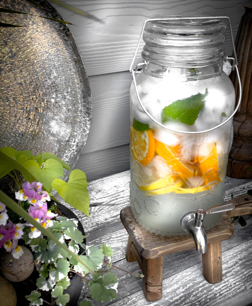 View of water container with orange and lemon slices in it.